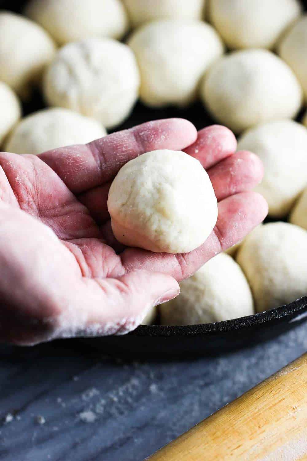 roll dough in a hand over a skillet of other rolled rolls for cheesy skillet rolls