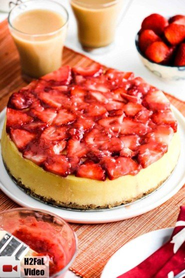 New York Style Cheesecake with strawberry glaze on a white plate with a cup off coffee.