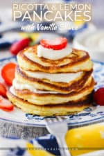 A stack of ricotta lemon pancakes on an antique plate with strawberries and a fork nearby.