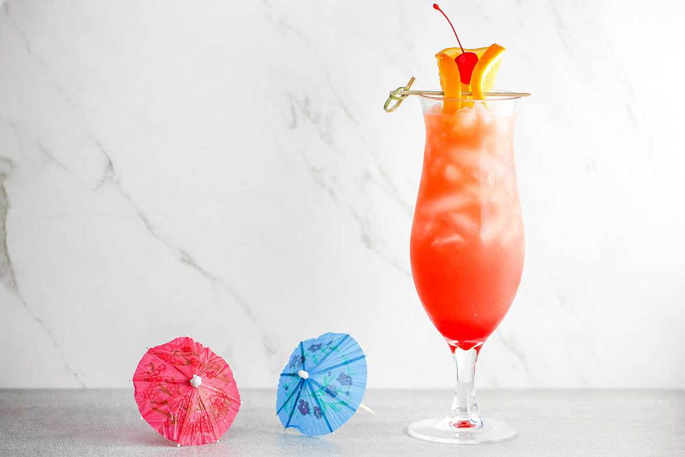 A hurricane drink in a tall glass with two small drink umbrellas next to the glass.