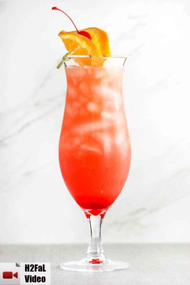 A hurricane cocktail in a tall glass with cherry and orange slice on top.