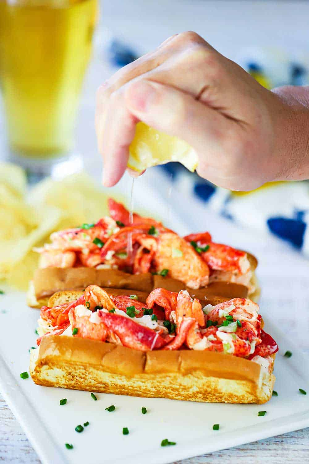 A hand squeezing a lemon wedge over the tops of two lobster rolls on a white plate.