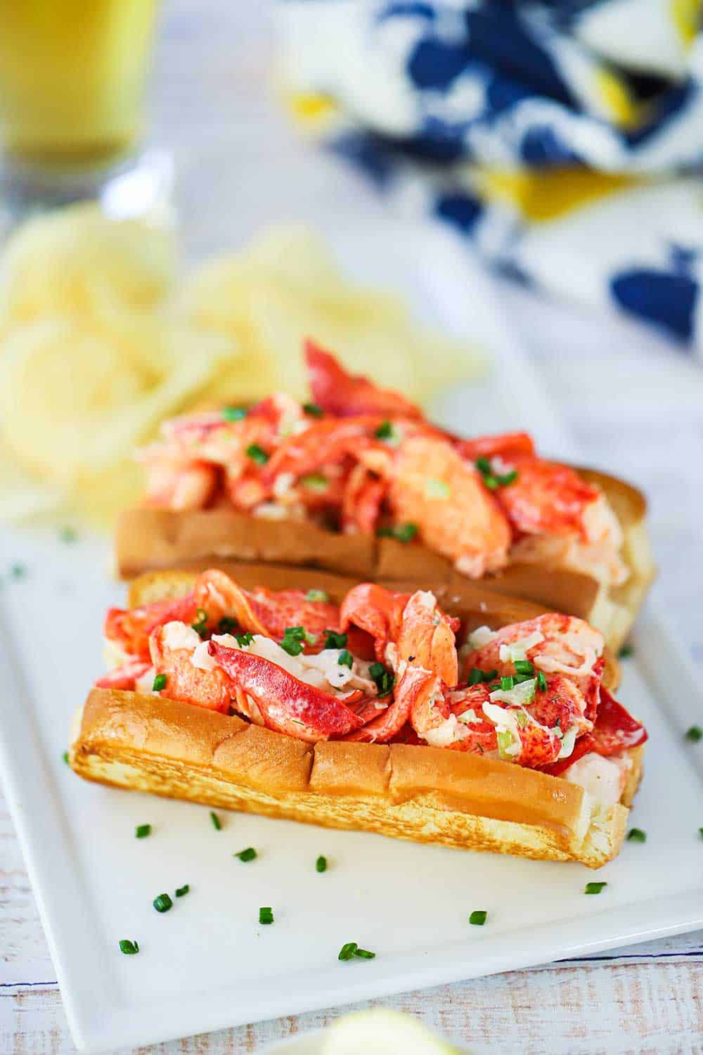 Two lobster rolls sitting on a rectangular white plate with snipped chives sprinkled over the top.