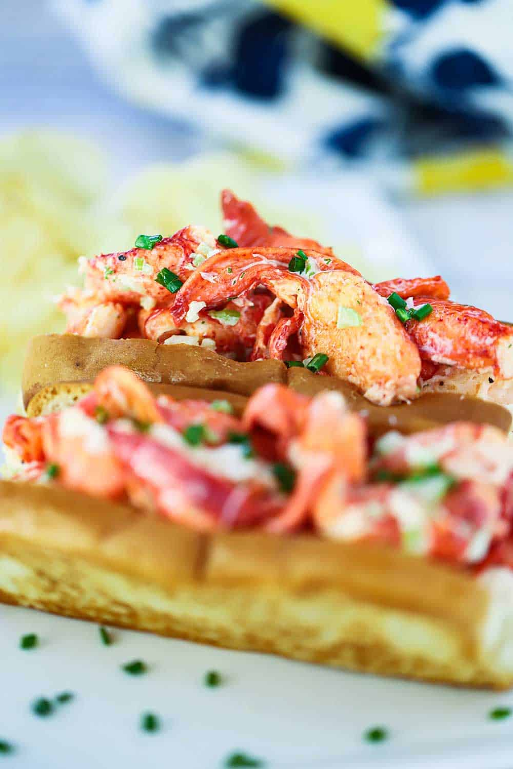 A close-up side view of two lobster rolls on toasted buns with snipped chives sprinkled over the tops.