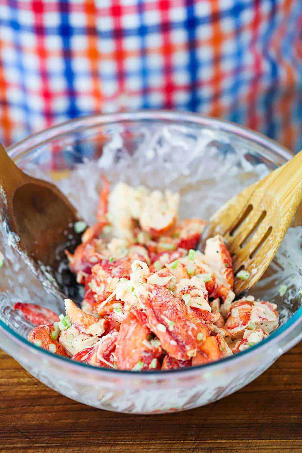 A glass bowl filled with lobster salad that is being tossed by a couple of wooden spoons.