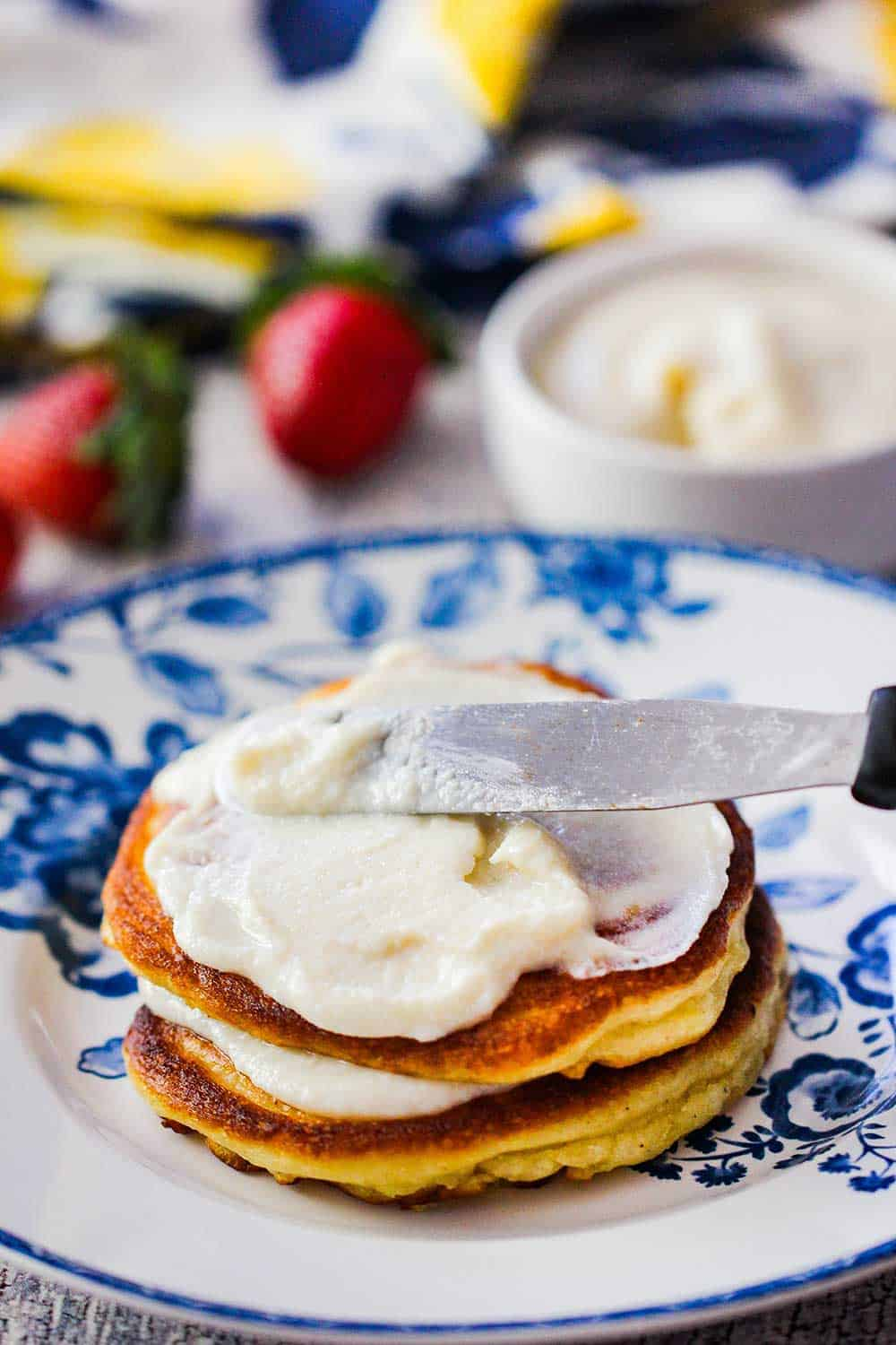 A knife smearing vanilla sauce onto lemon ricotta pancakes on a decorative plate.
