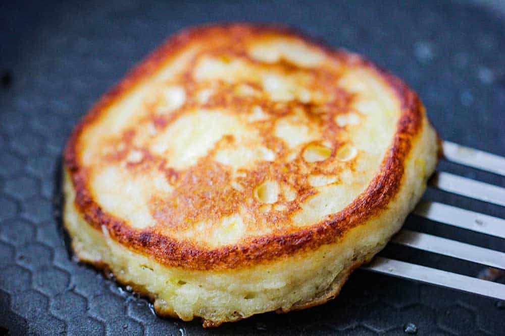 A perfectly cooked ricotta lemon pancake in a skillet with a spatula underneath it.