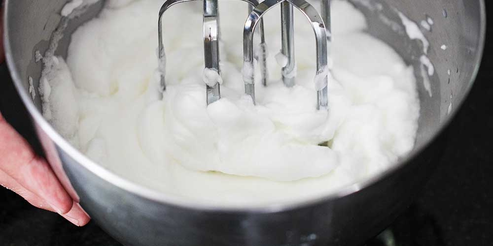 A close-up view of a hand mixer making stiff peaks from egg whites in a metal bowl.