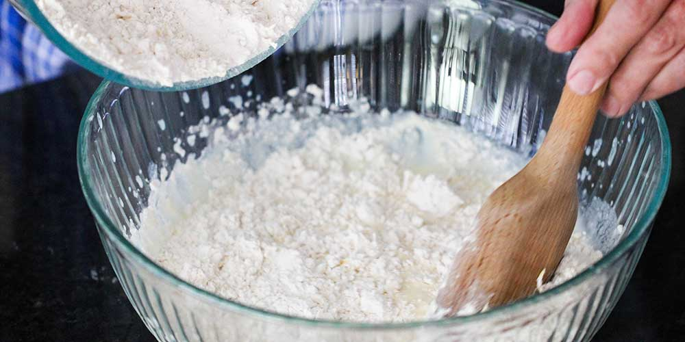 A wooden spoon mixing in a dry mixture into a wet mixture for ricotta lemon pancakes.