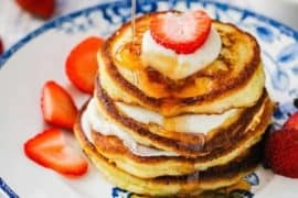 An antique plate holding ricotta pancakes with a strawberry on top and syrup being poured on top.