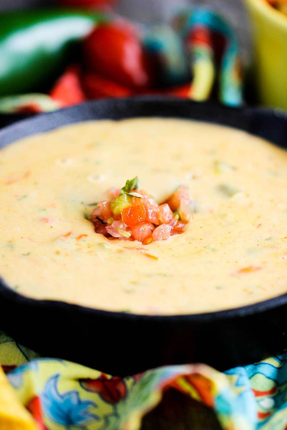 Classic Tex-Mex Queso in a cast iron dish with pico de gallo on top.