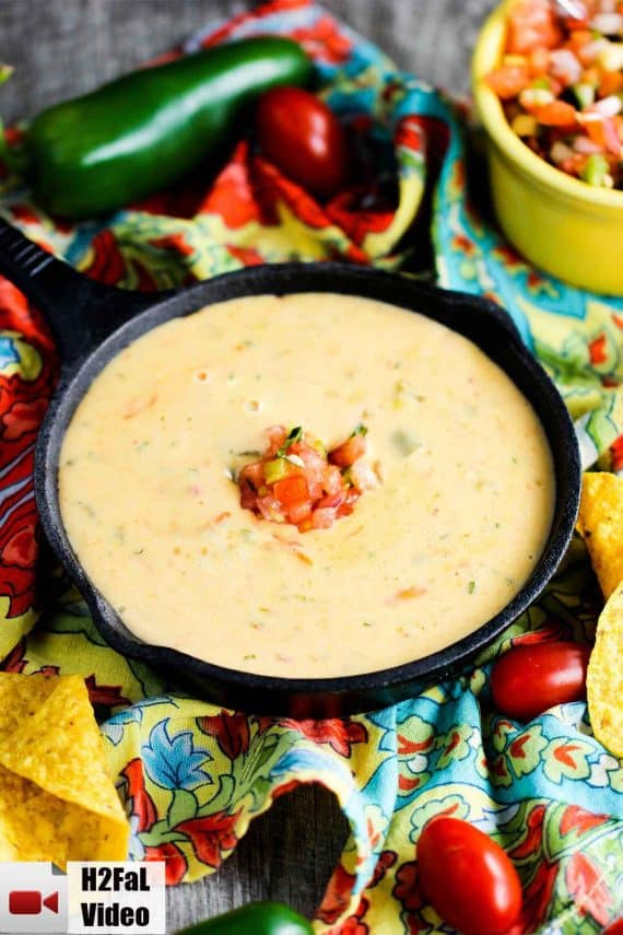 Classic Tex-Mex Queso in a small cast iron skillet surround by peppers and festive napkins.