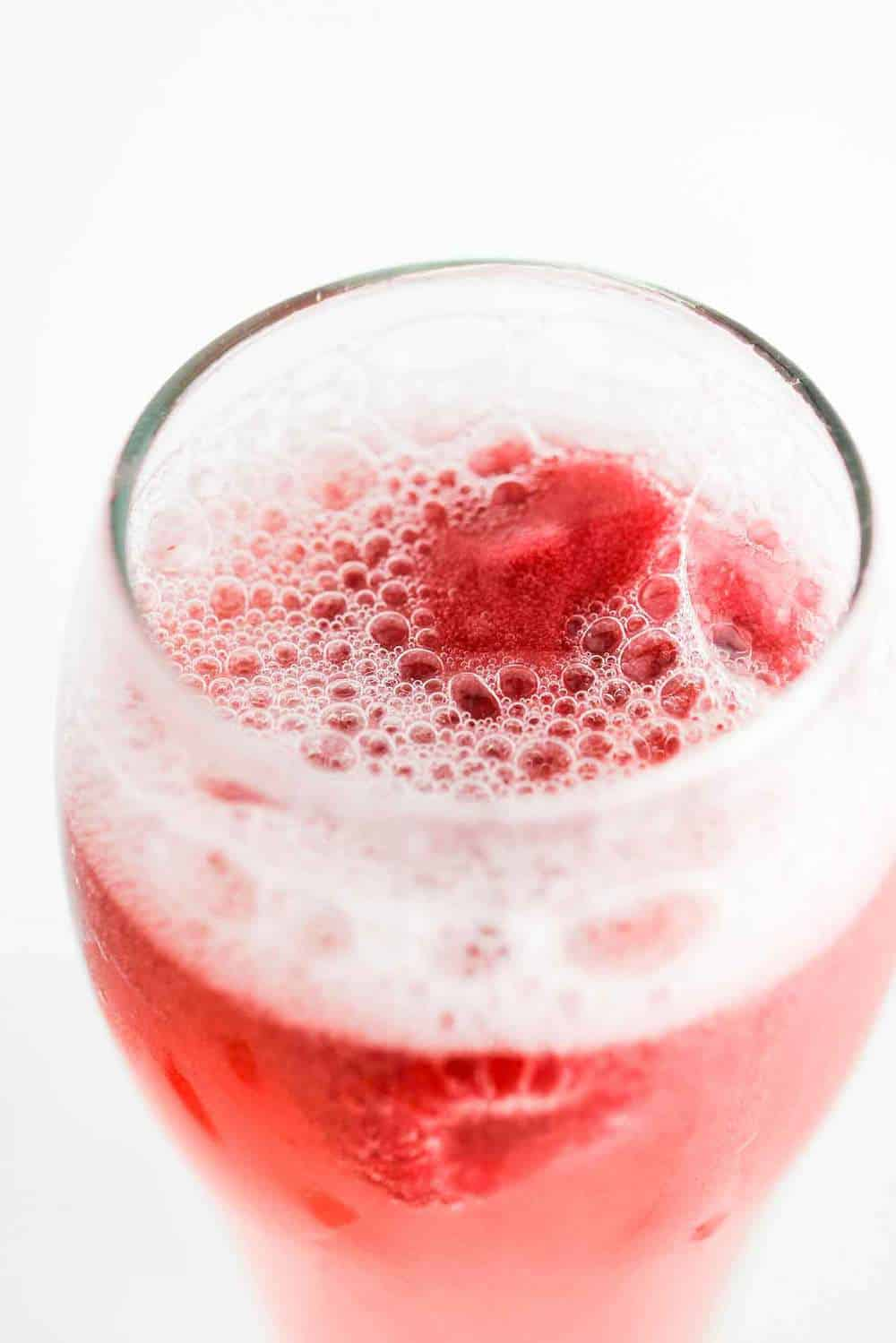 Overhead view of a sgroppino cocktail with a raspberry floating on top.