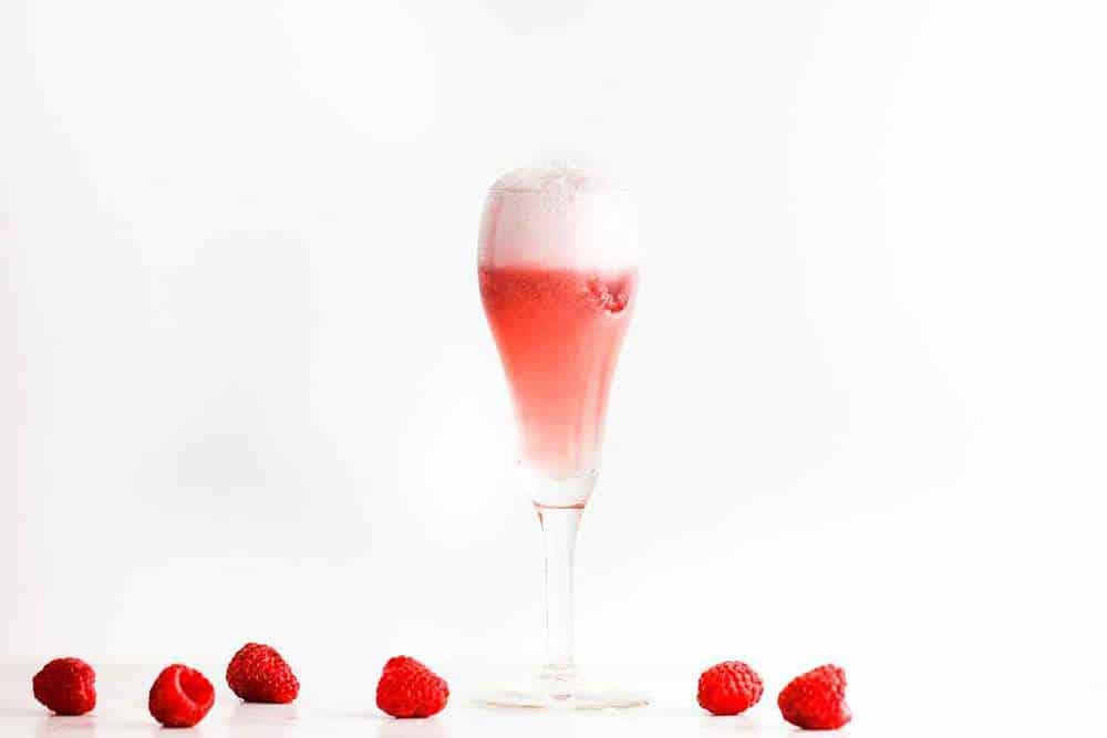 A sgroppino cocktail in a Champaign flute with raspberries sitting nearby.