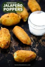 5 jalapeño poppers on a scratchy baking sheet next to a small jar of sour cream.