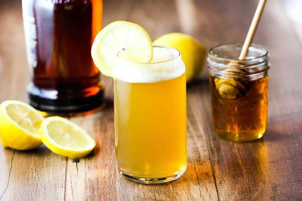 Bourbon and Honey Beer Cocktail with a jar of honey and a lime near by.