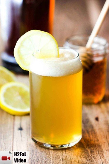 A bourbon and honey beer cocktail with a glass of honey next to it.