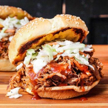 A slow-cooker pulled pork sandwich sitting on a wooden cutting board.
