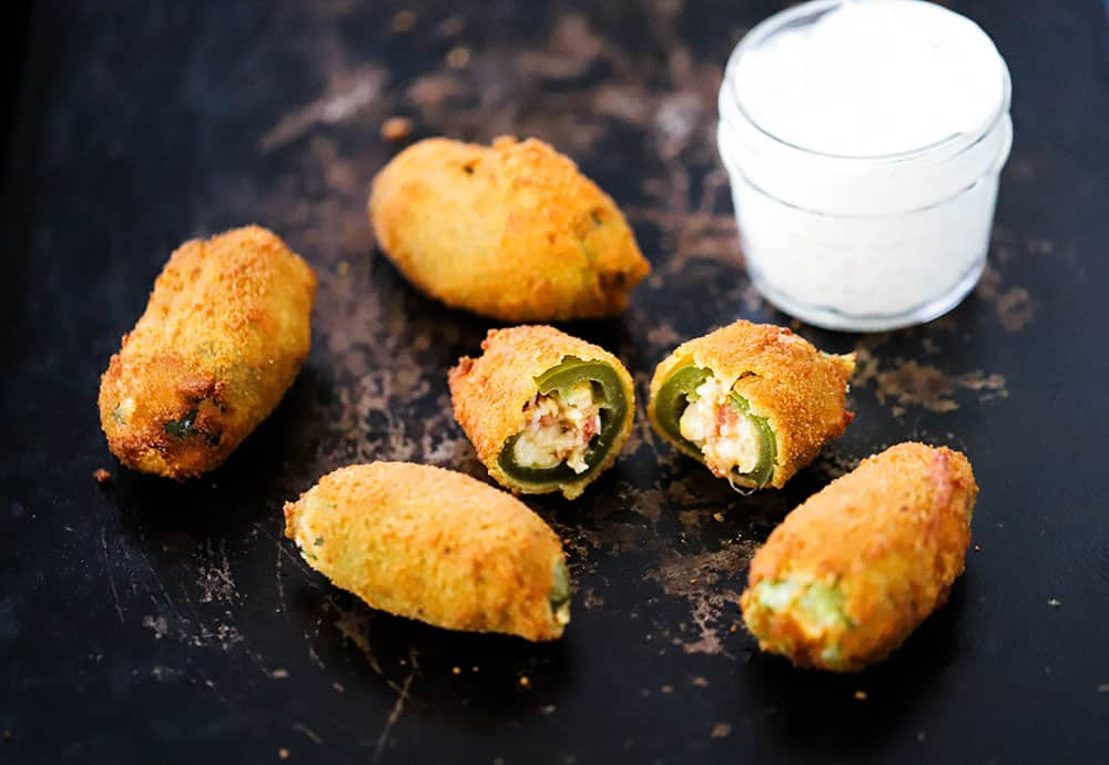 4 jalapeño poppers on a baking sheet with one split open and sitting next to a small jar of sour cream.