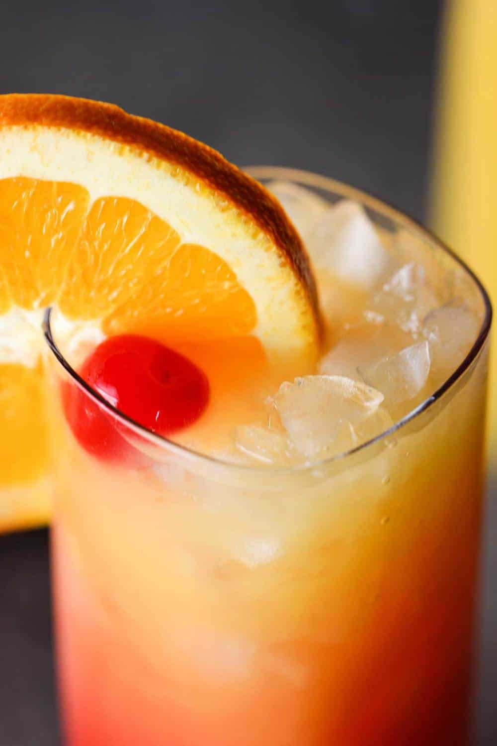 Close up shot of a tequila sunrise with a large wagon wheel orange garnish on the glass.