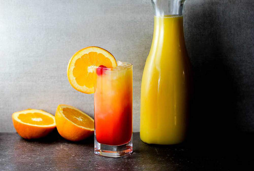 Classic Tequila Sunrise with oranges and fresh orange juice in the background.