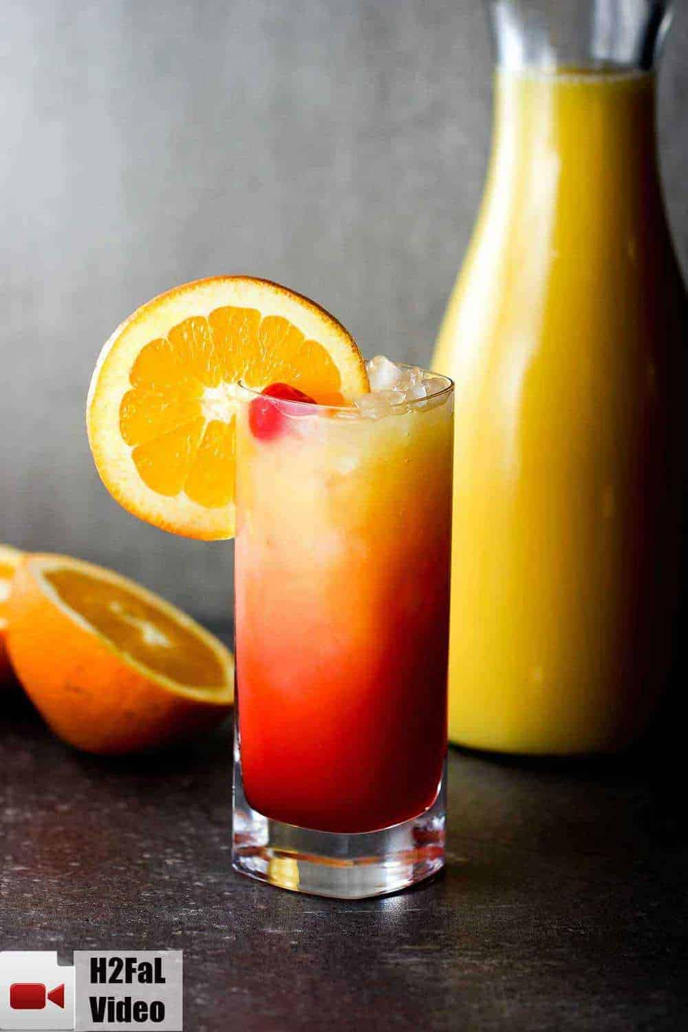 Classic tequila sunrise with an orange and bottle of juice nearby.