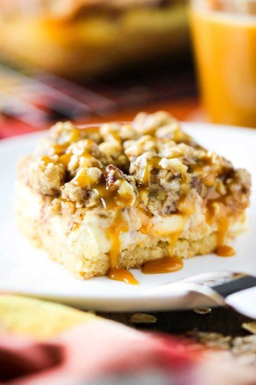 Cream cheese apple bars with pecan streusel on a white plate