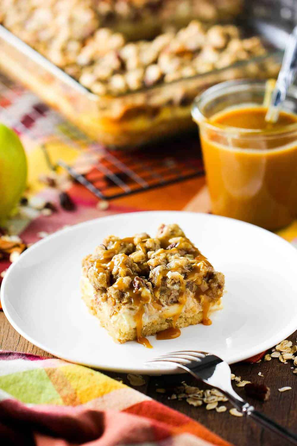 Cream cheese apple bars with pecan streusel on a white plate.