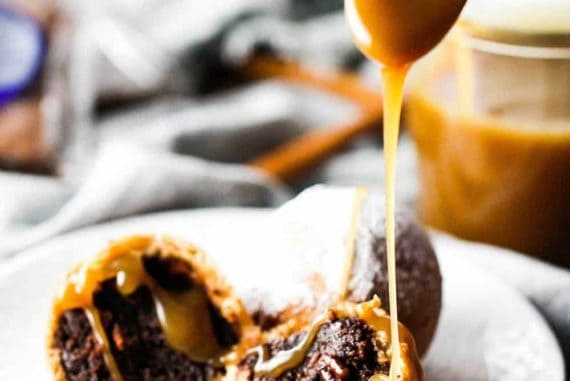 A spoon drizzling butterscotch over deep fried cinnamon cocoa brownies
