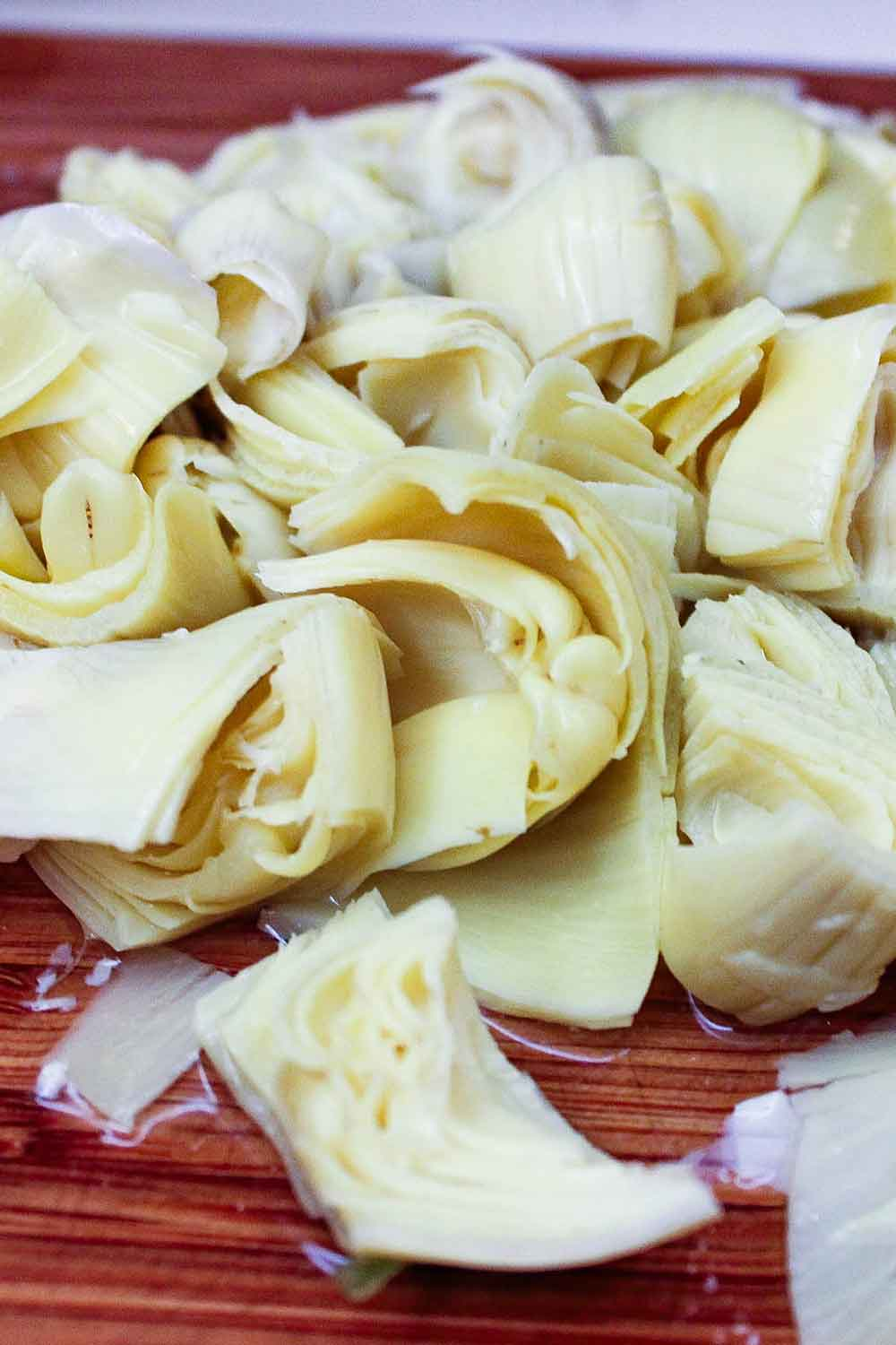Artichoke hearts on a wooden cutting board.