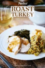 A white gravy boat pouring turkey gravy over a plate of mashed potatoes, dressing, turkey, and green beans.