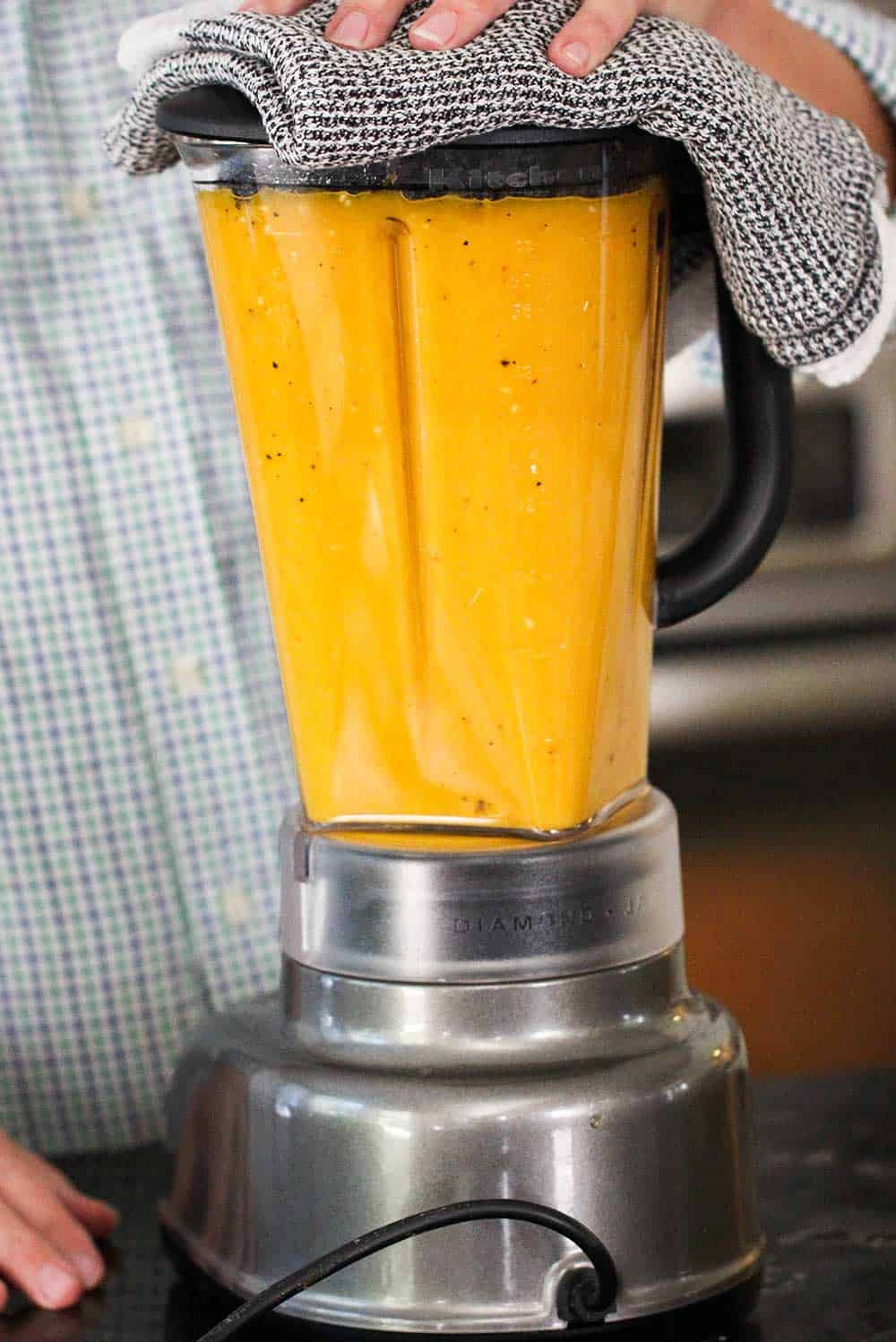 A blender full of roasted butternut squash soup that has been pureed.