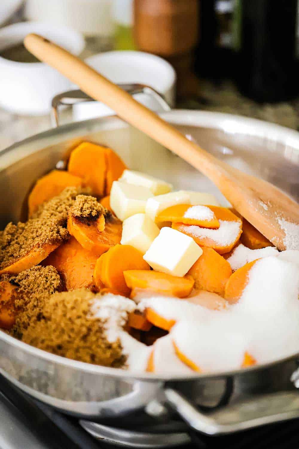 A large saucepan filled with sliced sweet potatoes, brown and white sugar, and sliced pieces of butter.