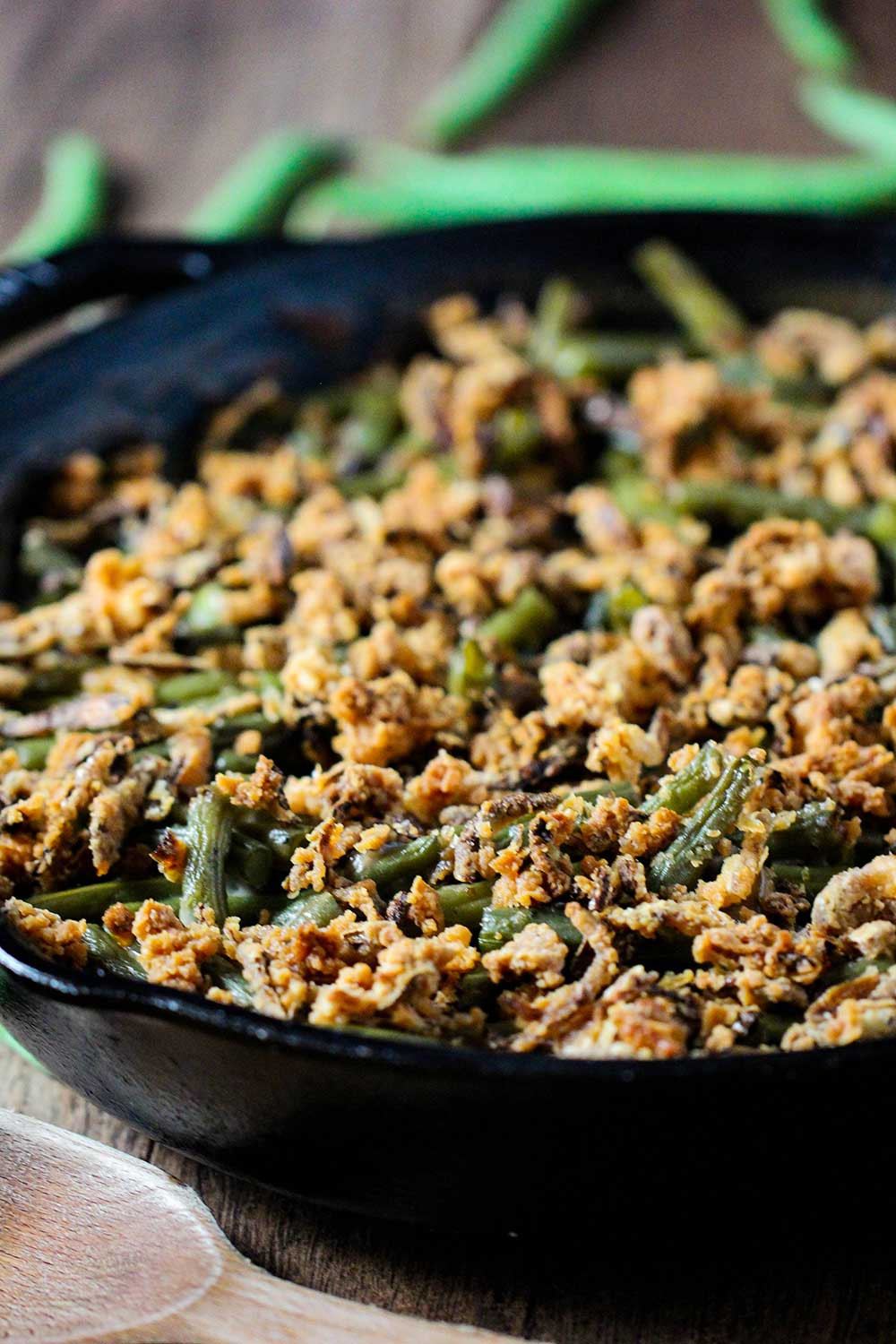 A large cast iron skillet holding gourmet green bean casserole with fresh green beans next to it.