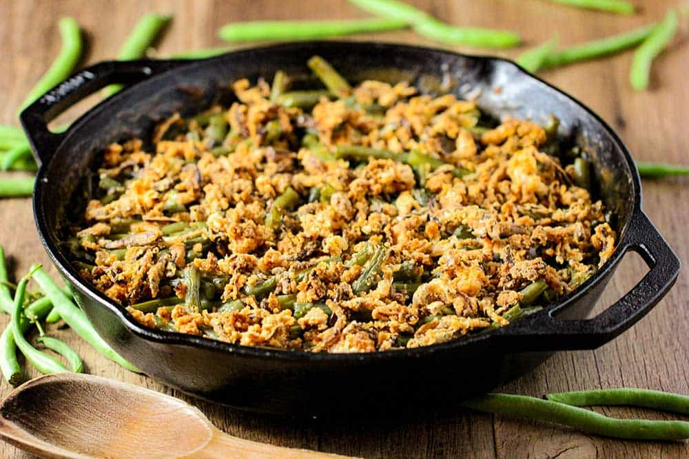 A large black cast iron skillet filled with green bean casserole with fresh green beans next to it.