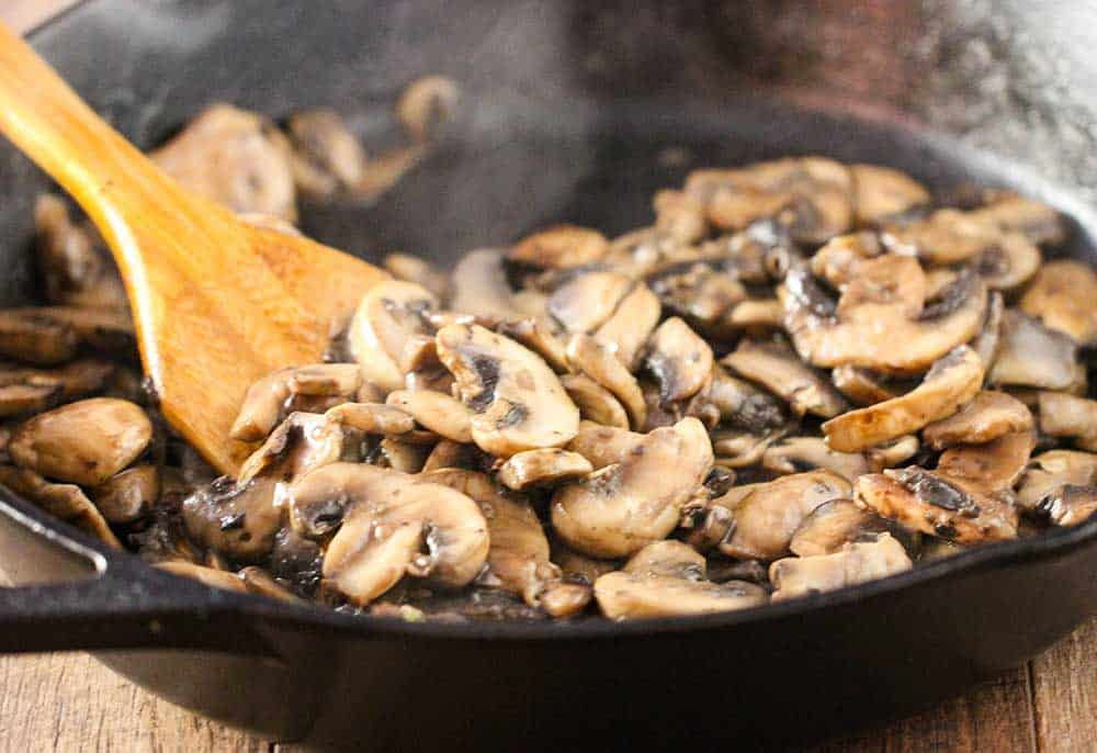 A large cast iron skillet filled with mushrooms being sautéed and moved around with a wooden spoon.