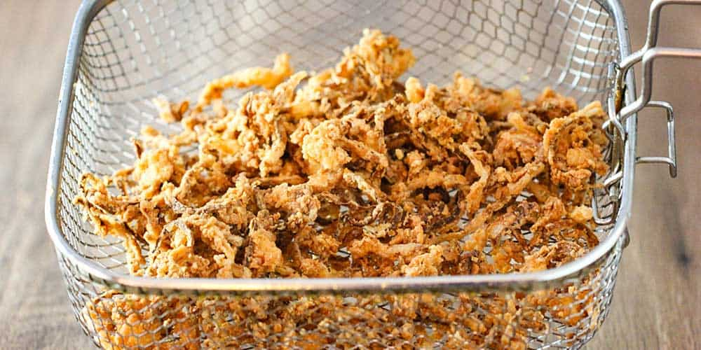 A fryer basket filled with fried onion strips.