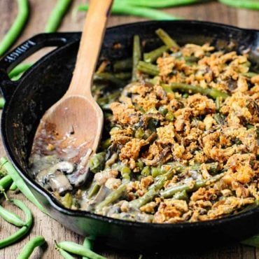 A large cast iron skillet filled with gourmet green bean casserole with a wooden spoon in it.