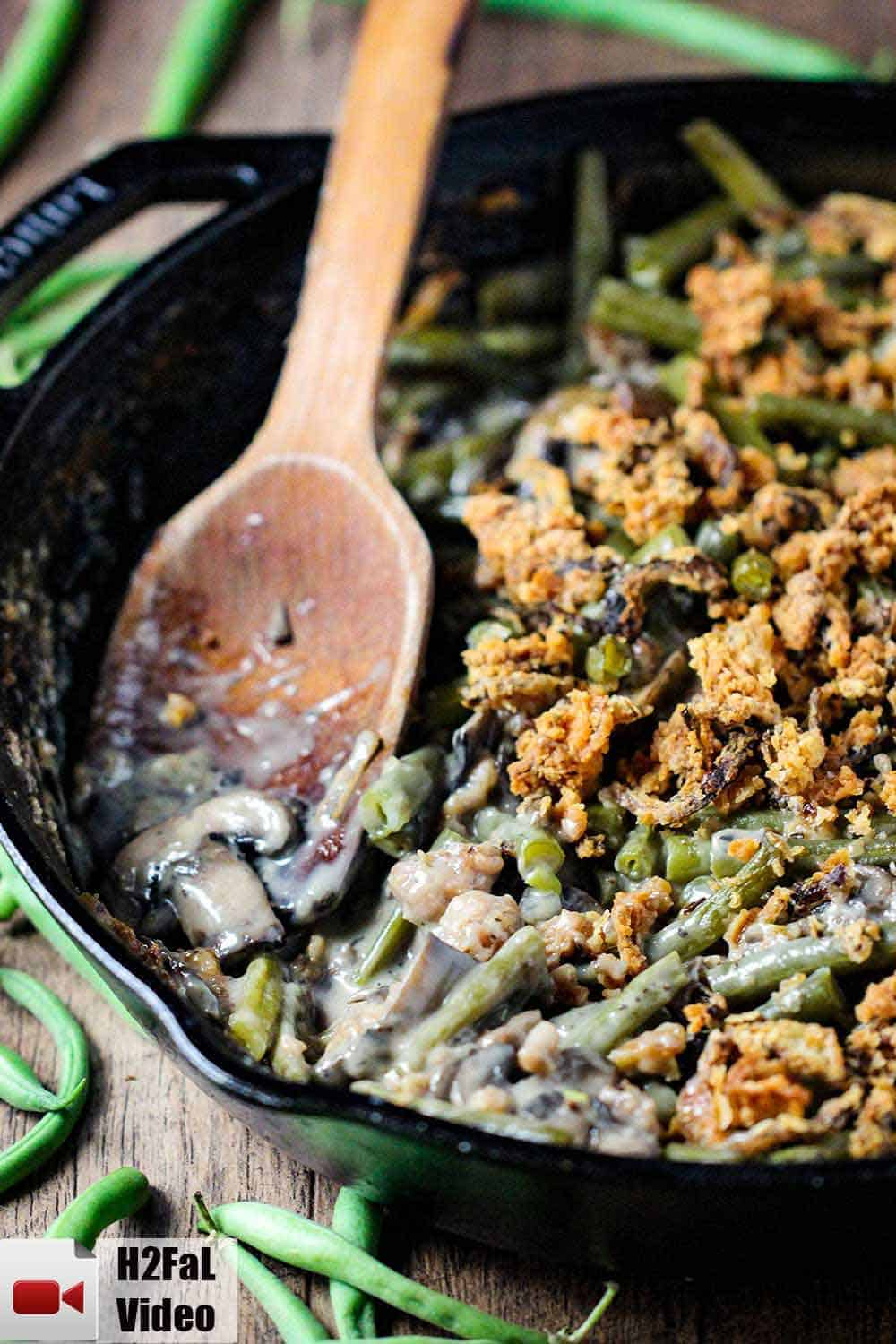 A large black cast iron skillet filled with gourmet green bean casserole with a wooden spoon in it.