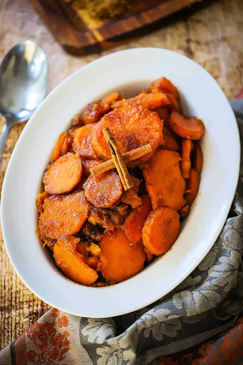 An oval serving dish filled with classic candied yams with two cinnamon sticks crossed on top.