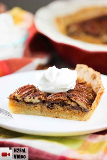 Classic Pecan Pie on a plate with whipped cream on top