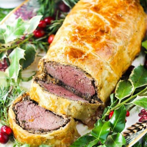 Classic Beef Wellington on a platter with Christmas holly around it