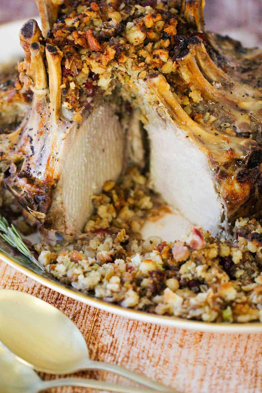 A crown roast of pork on a platter with stuffing.