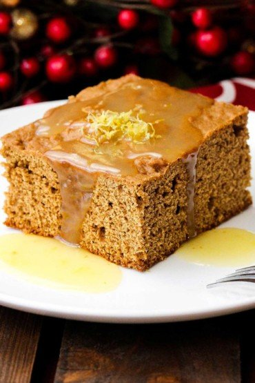 A white plate with a slice of Christmas Gingerbread Cake with Lemon Sauce