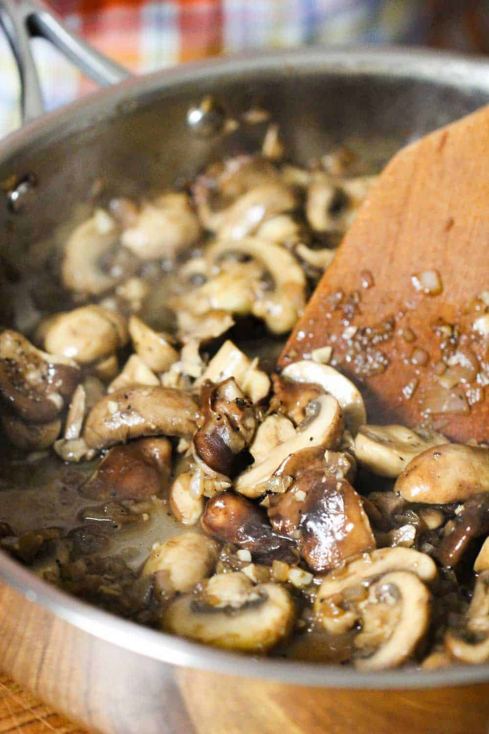 A large skillet with sautéed mushrooms in it being stirred by a wooden spoon.
