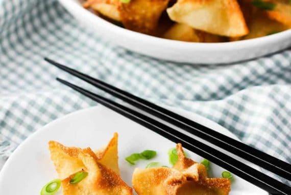 crab rangoon on a plate with chop sticks