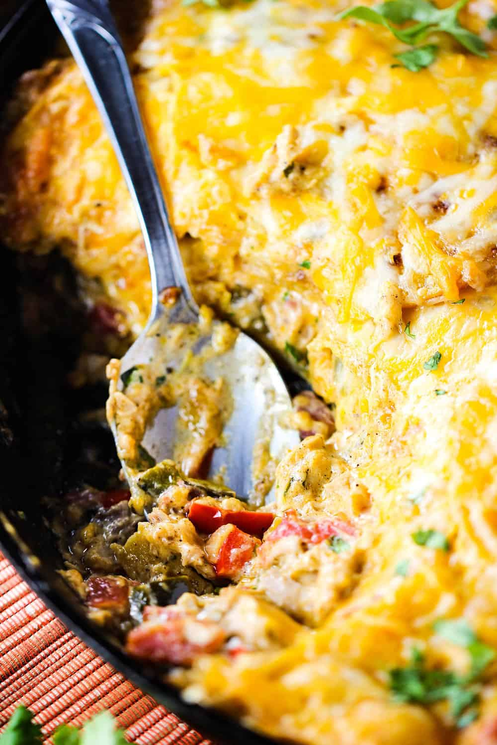 King Ranch casserole in a large cast iron skillet with a spoon in it