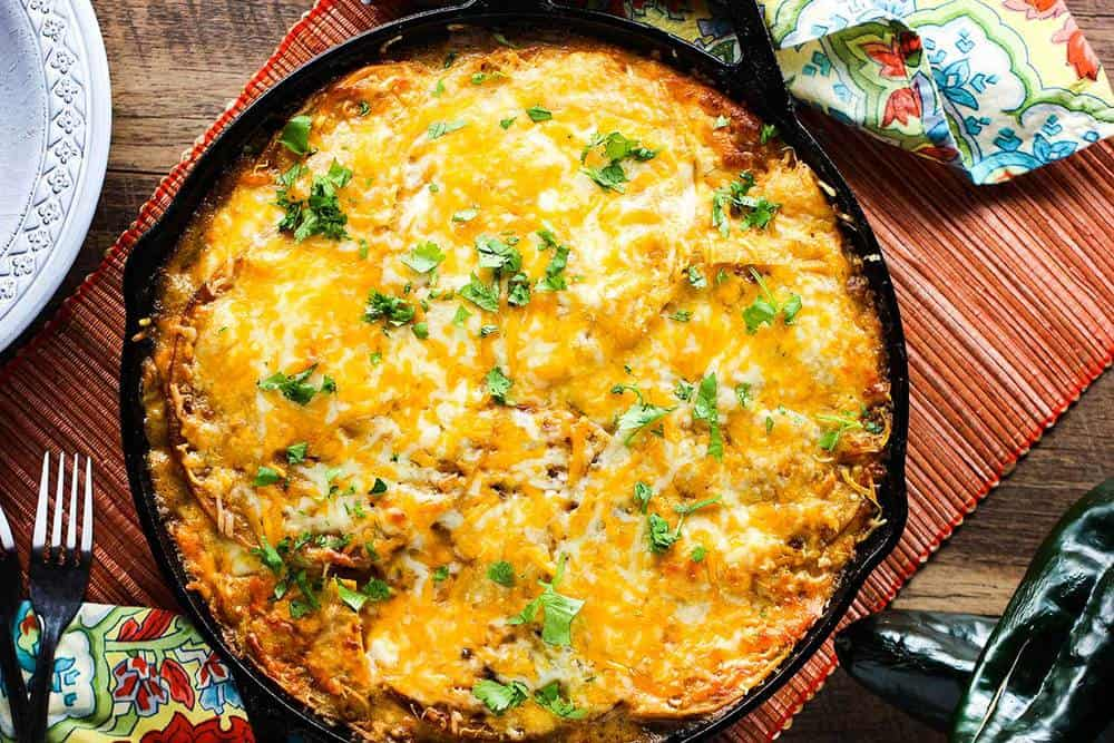 A large cast iron skillet of King Ranch Chicken Casserole next to festive napkins