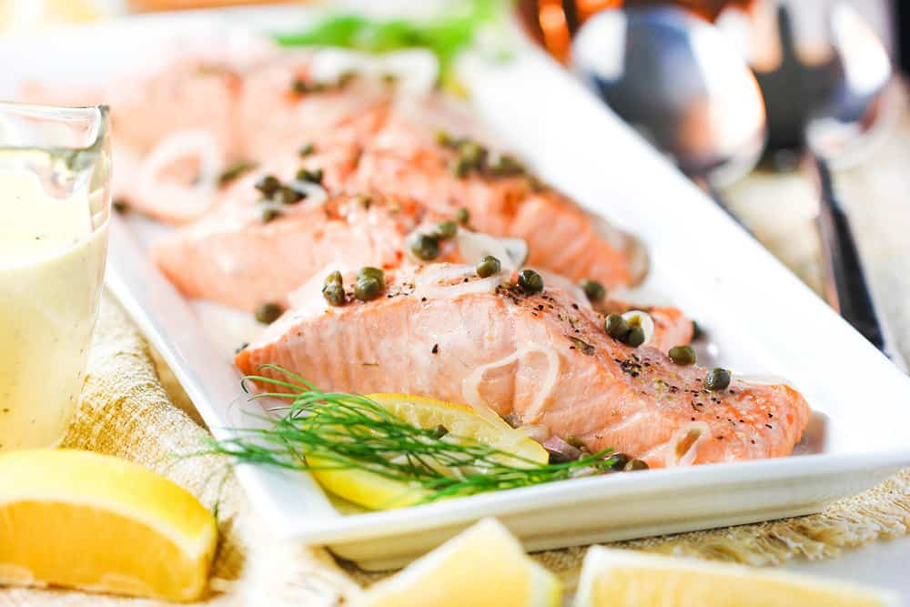 Poached salmon with capers and dill on a platter