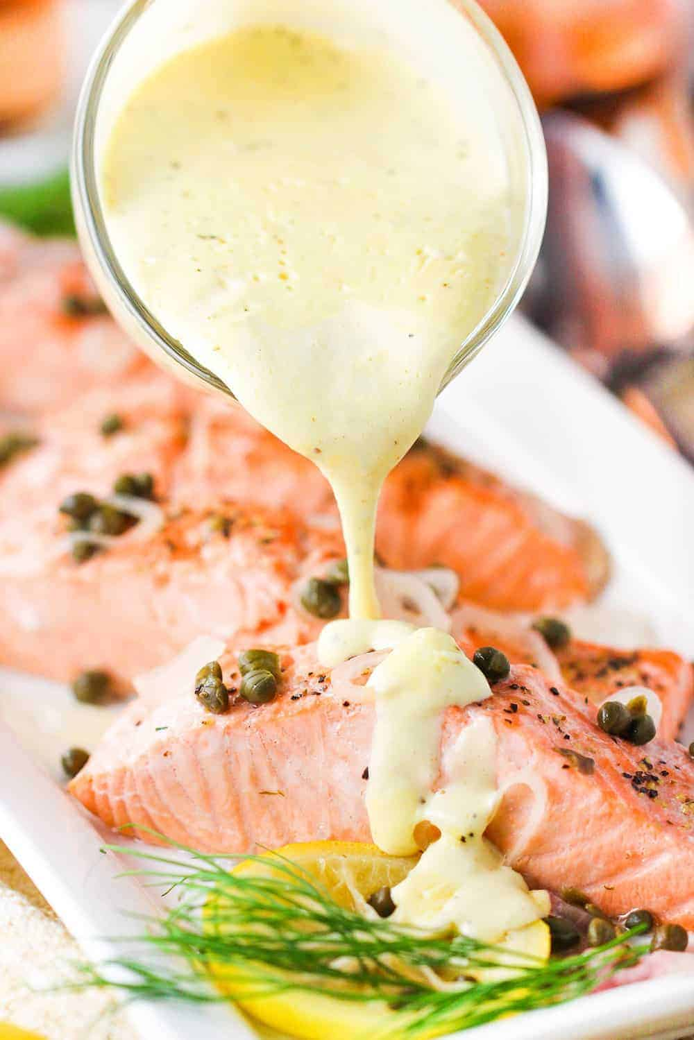 Poached salmon with hollandaise sauce being poured on top